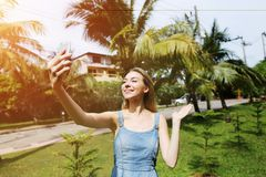 Sunshine portrait of young woman talking video call with smartphone and smiling on green palms background in Thailand. Bright portrait of young woman talking Royalty Free Stock Photos