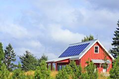 Sunshine Power. Bright red building with solar panels on the metal rooftop on a mostly sunny summer day in a public park stock images