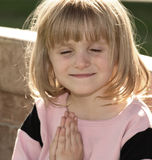 Sunshine Prayers. Little girl praying outside on a park bench Stock Photography
