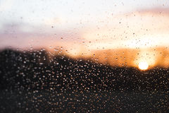 Sunset behind windowglass with raindrops