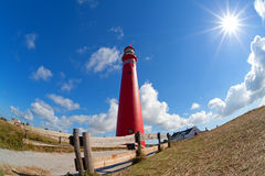 Sunshine and red lighthouse tower on coast Stock Images