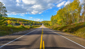 Sunshine road, single point perspective down a country highway in summer. Stock Photos