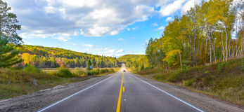 Sunshine road, single point perspective down a country highway in summer. Royalty Free Stock Photos