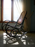 Sunshine Rocker. A rocking chair sits in front of a window where the sunlight streaming in causes patterns of shadows to fall on the carpet Royalty Free Stock Photo