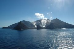 Sunshine on the sea surrounding a smoking volcano. White smoke and steam rise from a volcano. It is on an island surrounded by blue sea. The sea is calm. The royalty free stock image
