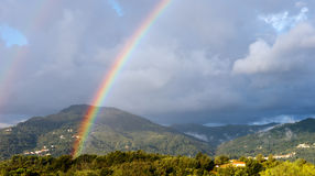 Sunshine and showers - weather rainbow landscape. Hilly rural sc Stock Photos