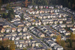 Sunshine on Small Suburban Development. Aerial view of family homes on the hillside at sunset Royalty Free Stock Image