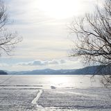 Sunshine on snow covered icy lake. Stock Photos