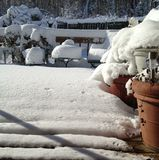 Sunshine sparkles off snow on back deck, chairs, and pottery. Royalty Free Stock Image