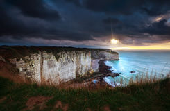 Sunshine and storm sky over cliffs in ocean Stock Photos