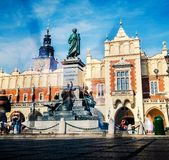 Sunshine view of monuments and ancient towers on the Krakow city central square. Sunshine view of bronze monuments on marble pedestal and ancient towers stock photos