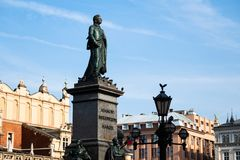 Sunshine view of monuments and ancient towers on the Krakow city central square. Sunshine view of bronze monuments on marble pedestal and ancient towers royalty free stock photo