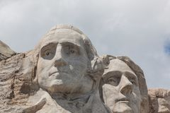 Mount Rushmore Close Up. Sunshine and white clouds provide a striking back drop for two of the carved faces of famous United States Presidents in Mount Rushmore stock photo