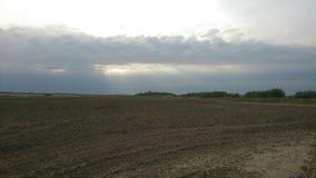 Sunshines dal cielo nuvoloso sopra il campo di agricoltura Immagini Stock