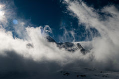 Sunshines through swirling clouds surrounding the mountain tops in Switzerland Stock Photo
