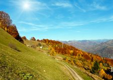 Sunshiny autumn Carpathian mountain, Rakhiv, Ukraine. Sunshiny autumn Carpathian Mountains landscape with multicolored yellow-orange-red-brown trees on slope and Royalty Free Stock Images