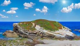 Sunshiny blossoming Atlantic coast Galicia. Summer blossoming Atlantic coast sunshiny landscape with pink flowers Islas beach, Spain. Two shots stitch high Stock Image