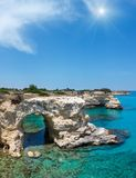 Sunshiny Faraglioni at Torre Sant Andrea, Italy. Picturesque sunshiny seascape with cliffs, rocky arch and stacks faraglioni, at Torre Sant Andrea, Salento sea Stock Image