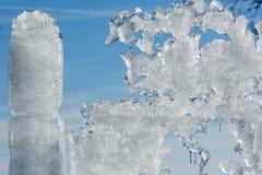 Sunshiny melting ice figure. Melting glacial block of ice on blue sky background Stock Photography