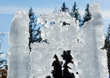 Sunshiny melting ice figure. The melting of the ice figure with icicles close-up on fir trees background Stock Photography