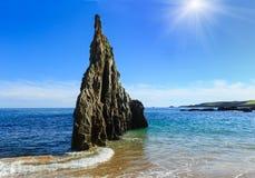 Sunshiny Mexota beach (Spain). Sunshiny Sandy Mexota beach and pointed rock (Spain). Atlantic Ocean coastline landscape Royalty Free Stock Image