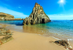 Sunshiny Mexota beach (Spain). Sunshiny Sandy Mexota beach and pointed rock (Spain). Atlantic Ocean coastline landscape Royalty Free Stock Photography