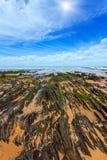 Sunshiny rocky sandy beach Portugal. Rock formations on sunshiny sandy beach and blue sky with cumulus clouds Algarve, Costa Vicentina, Portugal Royalty Free Stock Photos