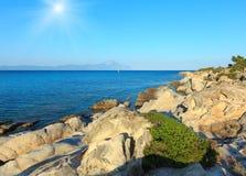 Sunshiny sea coast Chalkidiki, Greece. Aegean sunshiny sea coast landscape and Mount Athos in mist, view from Orange Beach Chalkidiki, Greece Royalty Free Stock Photography