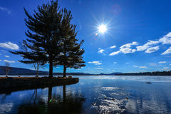 Sunstar blue sky and clouds at the lake Royalty Free Stock Photos
