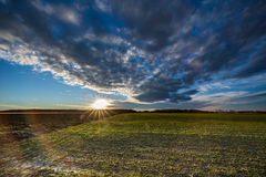 Sunstar at horizon unter dark clouds. Sunstar on the horizon on blue sky with ominous clouds over a field with rests of snow Royalty Free Stock Photos