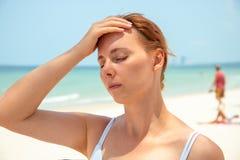 Sunstroke kobieta na pogodnej plaży Kobieta z migreną Gorący słońca niebezpieczeństwo Problem zdrowotny na wakacje obraz royalty free