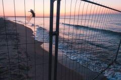Sunsut auf dem Strand auf dem Meer oder dem Ozean hinter dem Maschenzaun Stockfoto
