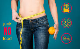 Sunt äta, bantar och konditionbegreppet Ingen skräpmat Sund kvinnlig kropp med apelsinen och mätabandet arkivfoto