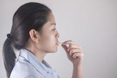 Sunt äta och bantar näringbegrepp Vitamin och tillägg härlig asiatisk ung kvinna som rymmer det gula pillret för fiskolja arkivbilder
