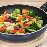 Sunt ätagrönsakmål i matlagningpanna Arkivbild
