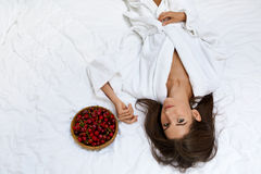 Sunt banta mat för kvinnans hälsa Flicka som äter frukter på säng fotografering för bildbyråer