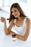 Sunt banta näring Kvinna som äter yoghurt, bär och sädesslag arkivfoto