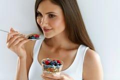 Sunt banta näring Kvinna som äter yoghurt, bär och sädesslag arkivbild