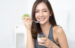 Sunt banta och n?ring Stående av den lyckliga härliga unga asiatiska kvinnan som hemma äter naturlig yoghurt och ser kameran fotografering för bildbyråer