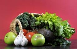 Sunt banta vård- foods med shoppingkorgen mycket av grönsaker Arkivbilder
