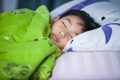 sunt barn Liten asiatisk pojke som fridfullt sover på säng Arkivbild