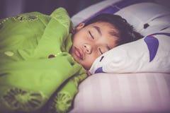 sunt barn Liten asiatisk pojke som fridfullt sover på säng Vint arkivfoton