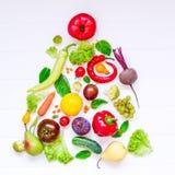 Sunt begrepp för nytt år - nya organiska grönsaker, örter och frukter i form av julträd på vit träbakgrund Di royaltyfria foton