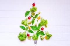 Sunt begrepp för nytt år - samling av nya organiska grönsaker och greeens i form av julträdet på vit träbakgrund arkivbild