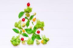 Sunt begrepp för nytt år - samling av nya organiska grönsaker och greeens i form av julträdet på vit träbakgrund Arkivfoton