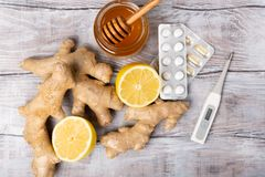 sunt begrepp Te, citron, termometer, ingefära, honung och minnestavlor på en vit bakgrund Lekmanna- lägenhet kall behandling arkivfoto