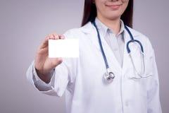 Sunt begrepp: Ung asiatisk doktor med affärskortet i handen, anonym framsida Arkivfoton
