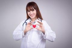 Sunt begrepp: Ung asiatisk doktor med röd hjärta i hand Arkivfoton