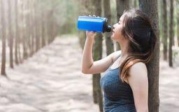 Sunt dricksvatten för härlig för sport för ung kvinna för flicka övning för livsstil, når att ha kört genomkörare royaltyfria bilder