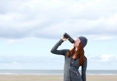 Sunt dricksvatten för ung kvinna från flaskan Arkivfoto
